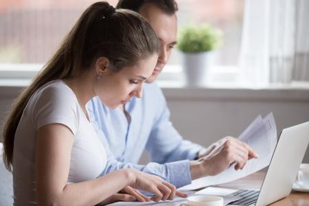 Una coppia millenaria seria legge documenti che gestiscono le bollette della casa, l'uomo e la donna analizzano l'avviso bancario o l'assicurazione considerando i termini, marito e moglie tengono documenti per il calcolo delle finanze o del budget