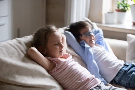 Cute little kids lying with eyes closed on cozy couch hands over head, little boy and girl taking nap relaxing on comfortable sofa in living room, funny siblings act like adults copying parents rest Banco de Imagens