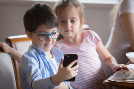 Small boy holding smartphone making picture or playing game, curious little girl looking at video on phone shown by brother, cute kids having fun watching cartoon on mobile during breakfast in kitchen Banque d'images - 107735252