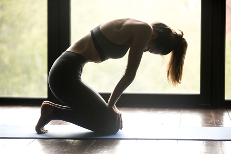 Young sporty woman practicing yoga, doing breathing exercise, Uddiyana Bandha pose, working out, wearing sportswear, grey pants and top, indoor full length, yoga studio. Side view