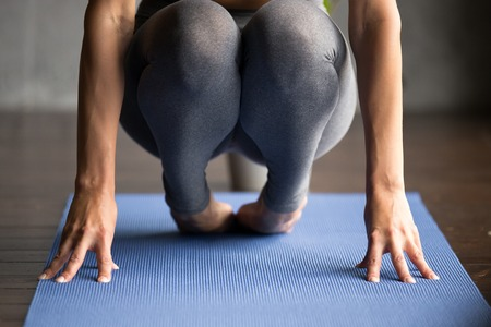 Sporty woman practicing yoga, doing foot strengthening exercise, healing physical therapy pose, working out, wearing sportswear, grey pants, indoor close up, yoga studio Фото со стока