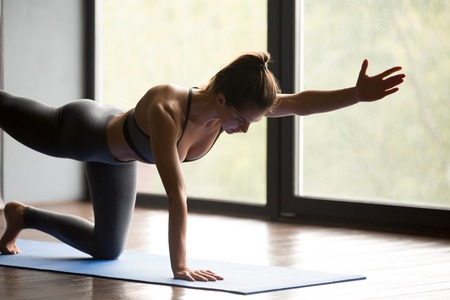 Young sporty woman practicing yoga, doing Donkey, Kick exercise, Bird dog pose, working out, wearing sportswear, grey pants and top, indoor, yoga studio Stock Photo
