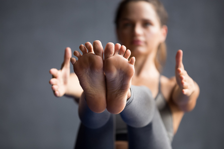 Young sporty woman practicing yoga, doing Paripurna Navasana exercise, boat pose, working out wearing sportswear grey pants, working out, indoor close up view of legs, yoga studio, focus on feet Stock Photo