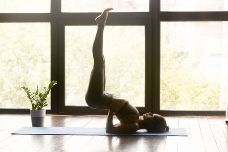 Young sporty woman practicing yoga, doing exercise, Viparita Karani pose, working out, wearing sportswear, grey pants and top, indoor full length, yoga studio. Side view