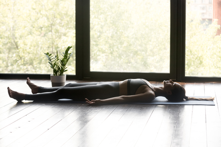 Young sporty woman practicing yoga, doing Dead Body, Savasana exercise, Corpse pose, working out, wearing sportswear, grey pants and top, indoor full length, yoga studio Stock Photo