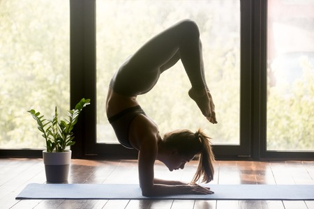 Young sporty woman practicing yoga, doing vrischikasana exercise, Scorpion pose, working out, wearing sportswear, grey pants and top, indoor full length, yoga studio