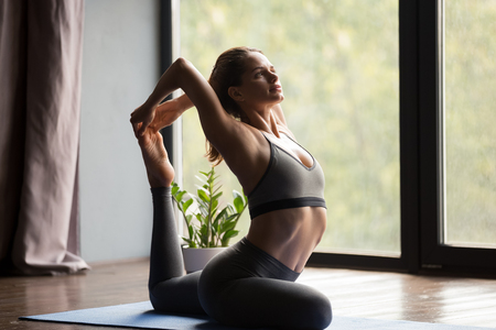 Young sporty attractive woman practicing yoga, doing One Legged King Pigeon exercise, Eka Pada Rajakapotasana pose, working out, wearing sportswear, grey pants and top, indoor full length, yoga studio