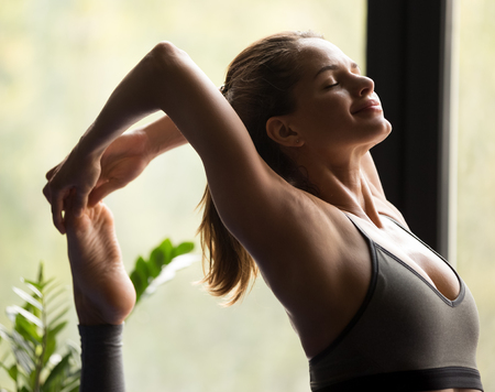 Young smiling sporty woman practicing yoga, doing One Legged King Pigeon exercise, Eka Pada Raja kapotasana pose, working out, wearing sportswear, grey pants and top, indoor close up, yoga studio