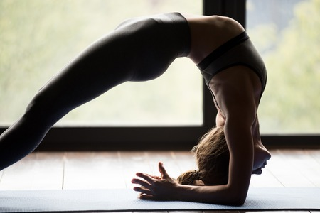 Young sporty woman practicing yoga, doing Elbow Bridge exercise, Dvi Pada Viparita Dandasana pose, working out, wearing sportswear, grey pants and top, indoor, body close up view, yoga studio 写真素材