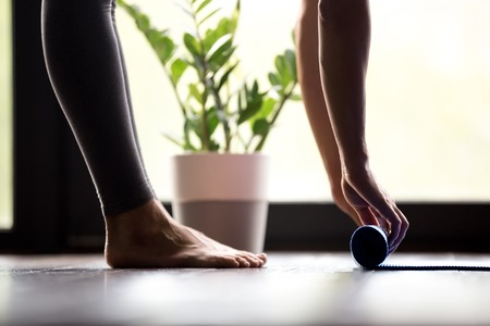 Woman unrolling mat, surface to perform yoga exercises at yoga studio, preparing sport equipment for before or after practicing yoga and working out, indoor close up
