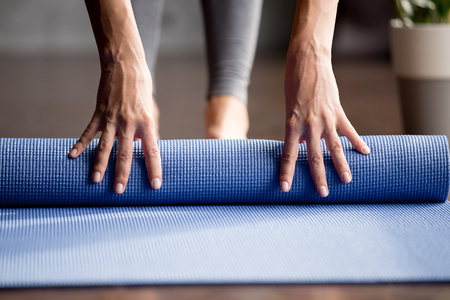 Time for meditation session or fitness practice concept. Close up view of fit beautiful woman rolling fitness, pilates or yoga mat before or after working out in yoga studio club or at home on floor