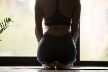 Sporty beautiful woman practicing yoga, doing seiza exercise, thunderbolt, vajrasana pose, working out, wearing grey sportswear pants, body close up rear view, indoor yoga studio, wellness concept