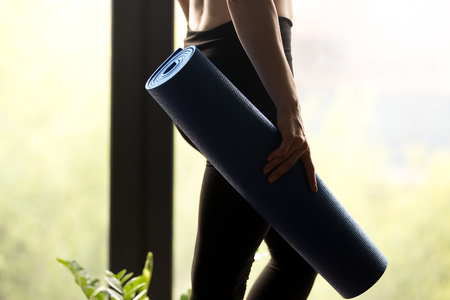 Sporty woman holding yoga mat, ready for yoga practice and sport exercise, before working out, wearing sportswear black pants, yoga indoor studio, body and legs close up view. Well being concept