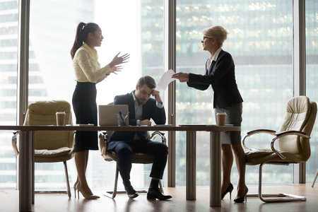 Dissatisfied, angry director business woman criticizing work, financial report, accusing woman and man workers. Subordinate feels guilty and frustrated. Conflict, problems mistakes and dismiss concept