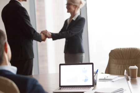 Multiracial businesspeople at meeting. Director welcomes new colleague, hr. Acquaintance and greeting, reward, focus on computer on desk. Client and executor shaking hand after successful deal concept Фото со стока