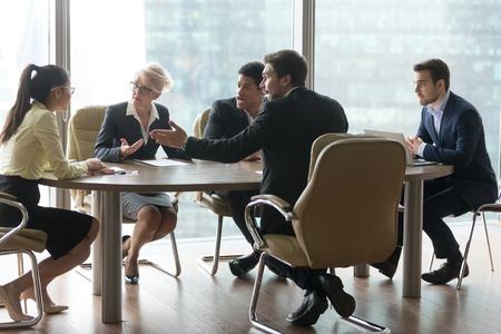 Groupe multiracial de travailleurs se disputant au bureau lors d'une réunion. Insatisfait collègue patron expliquant argumenter critiquer le travail de la jeune fille asiatique stagiaire. Problèmes erreurs dans le concept de travail Banque d'images