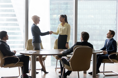Smiling multiracial business people at meeting. Mature woman ceo welcomes new colleague greeting, reward or promotion. HR, Client and executor shaking hands. Encourage, retirement and respect concept Фото со стока