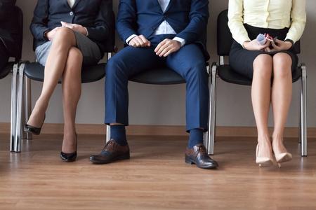Mensen uit het bedrijfsleven zitten in stoelen in de rij te wachten op hun beurt voor een sollicitatiegesprek. Groep kandidaten voor één functie tot bedrijf. Human resources, hr, wervingsconcept. De benen van mensen sluiten omhoog