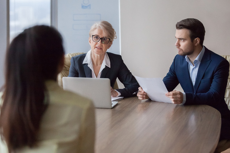 Businesswoman and businessman HR manager interviewing woman. Candidate female for company position sitting her back to camera, focus on interviewers. Human resources, hr, recruitment, hiring concept