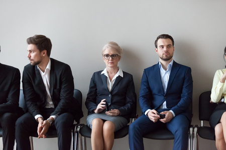 Group of serious young and middle aged candidates professionals business people sitting in chairs in queue waiting job interview, for one position at company. Human resources, hr, recruitment concept Banco de Imagens