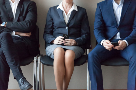 Close up business people sitting in chairs in queue waiting job interview. Candidates for one position to company. Human resources, workplace inequality, discrimination based on person gender concept Stockfoto