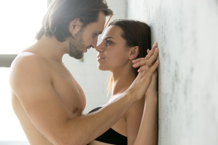 Sensual couple holding hands looking in the eyes leaning on wall, passionate lovers enjoy tender romantic moment in bedroom, man get closer admiring girlfriend almost kissing having sex foreplay Stock Photo