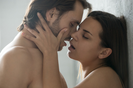 Close up of sensual millennial couple enjoying hot foreplay standing near wall, passionate lovers kissing and caressing, touching and teasing each other before making love, man and woman have intimacy