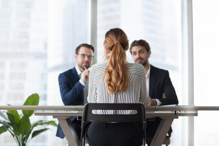 Back view of woman candidate interview with male HR managers in modern office, thoughtful recruiters think about female applicant candidature, doubting recruiters consider employee experience Фото со стока - 108467395