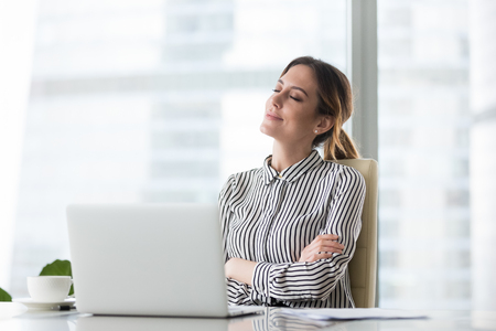 Smiling businesswoman sitting in office chair relaxing with eyes closed, calm female worker or woman ceo feeling peaceful resting at workplace dreaming about positive things distracted from work Imagens