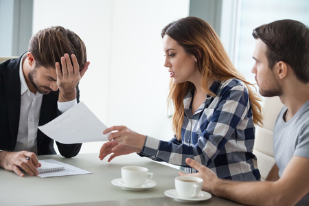 Dissatisfied wife have dispute with realtor or broker in office discussing contract mistakes or terms, consultant feel annoyed or bothered by angry woman proving document incorrect at meeting Stock Photo