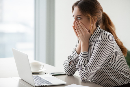 Shocked woman worker looking at laptop screen surprised with bad or unexpected online news, amazed businesswoman feel despair rounding eyes witnessing company bankruptcy or market failure