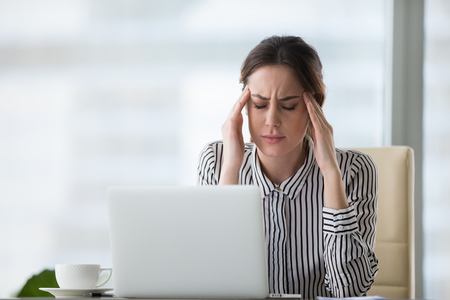Exhausted businesswoman massaging temples suffering from headache at workplace, tired female CEO meditating relieving stress or pain working long hours, woman worker having health problems