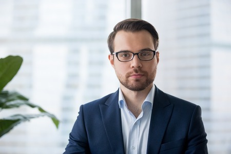 Portrait of serious millennial businessman wearing glasses looking at camera, headshot of concentrated confident male worker or director posing in modern office, making photo or picture near window Banco de Imagens - 108467466