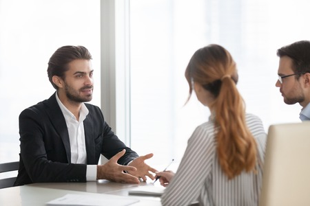 Confident millennial male job applicant talk at interview in office, HR team listen seriously to man employee at hiring process in boardroom, considering candidature. Recruitment, employment concept Banque d'images - 108467467