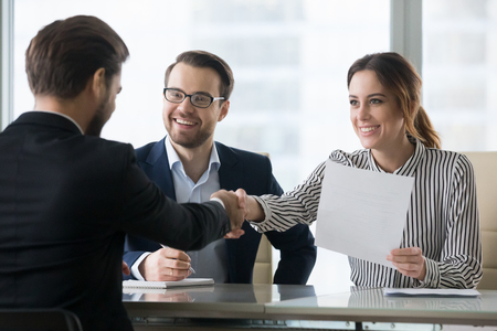 Happy employers shake hand of male job candidate, congratulating with given position, satisfied HR managers happy to hire applicant handshake greeting at team. Successful good interview concept 写真素材