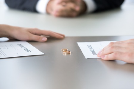 Close up of marriage rings lying on table along with divorce decrees and couple hands, husband and wife sign paper separating or breaking up officially, spouses end relationships at lawyer office Stock fotó