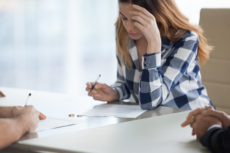 Serious millennial wife sign decree paper filing for divorce with husband visiting lawyer office, spouses end unsuccessful marriage put signature on document, man and woman get separated. Close up Stock Photo