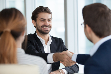 Close up view of HR managers handshake smiling male job candidate congratulating with hiring, happy satisfied employee shake hand employers greeting him, thanking for good interview, welcoming at work