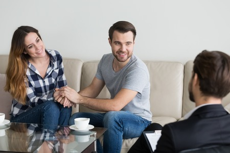 Happy couple sit on couch holding hands, look at psychologist thanking for saving marriage, loving husband and wife reconciled at therapy session, relationship expert help spouses to make peace Reklamní fotografie - 108469478