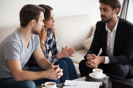Millennial couple meet with realtor or broker talking about home purchase, husband and wife visit agent discussing buying house together or taking loan for first apartment, family counselling