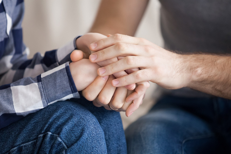 Close up of reconciled husband and wife holding hands showing support and love, couple make peace after fight hugging and caressing, man embrace woman comforting her, overcoming problems together Stock Photo