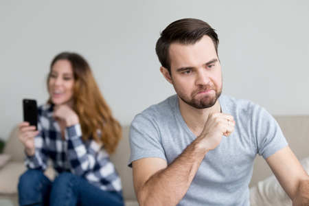 Angry husband feel jealous of happy wife texting on phone to somebody, mad man furious about beloved woman having fun, suspect spouse in cheating, thinking about divorce. Relationships problem concept