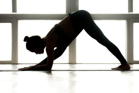 Young sporty attractive woman practicing yoga, doing One Sided Fold exercise, Parsvottanasana, Pyramid pose, working out, wearing sportswear, indoor full length, at yoga studio, side view silhouette