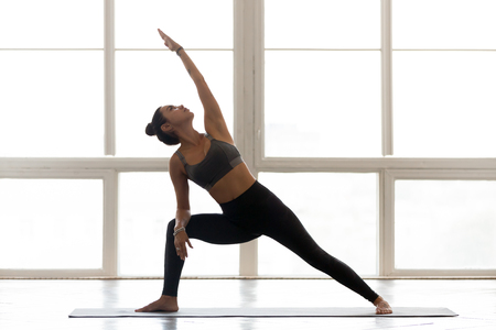 Young sporty attractive woman practicing yoga, doing Reverse Warrior exercise, Viparita Virabhadrasana pose, working out, wearing sportswear, grey pants, top, indoor full length, at yoga studio