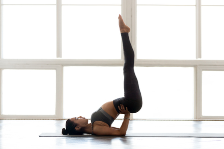 Young sporty attractive woman practicing yoga, doing Viparita Karani exercise, upside-down pose, working out, wearing sportswear, grey pants, top, indoor full length, at yoga studio