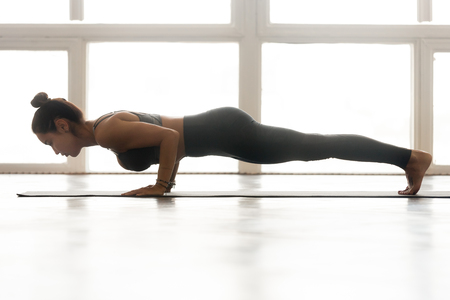 Young attractive woman practicing yoga, doing four limbed staff exercise, Push ups or press ups, chaturanga dandasana pose, working out wearing sportswear, indoor full length at yoga studio, side view