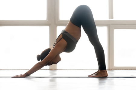 Young sporty attractive woman practicing yoga, doing Downward facing dog exercise, adho mukha svanasana pose, working out, wearing sportswear, grey pants, top, indoor full length, at yoga studio