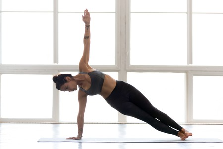 Young yogi attractive woman practicing yoga, doing Vasisthasana exercise, Side Plank pose, working out, wearing sportswear, grey pants, top, indoor full length, at yoga studio Stock Photo
