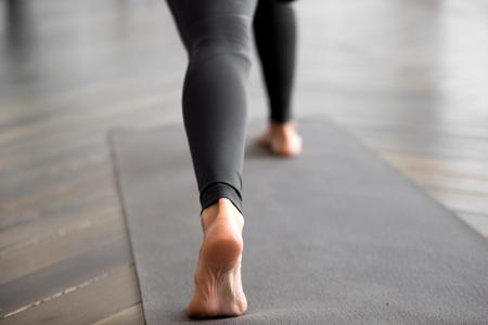 Mujer deportiva practicando fitness, haciendo ejercicio, pose de yoga, ejercitándose en la estera de yoga, vistiendo pantalones negros de ropa deportiva, interior de cerca, en el estudio de yoga, se centran en un talón. Bienestar, concepto de vida saludable