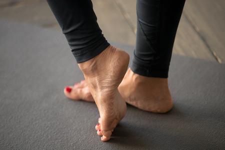 Sportowa aktywna kobieta uprawiająca jogę, wykonująca ćwiczenia wzmacniające mięśnie stopy, kostki, ćwiczenia, noszenie odzieży sportowej, zbliżenie w pomieszczeniach, w studio jogi